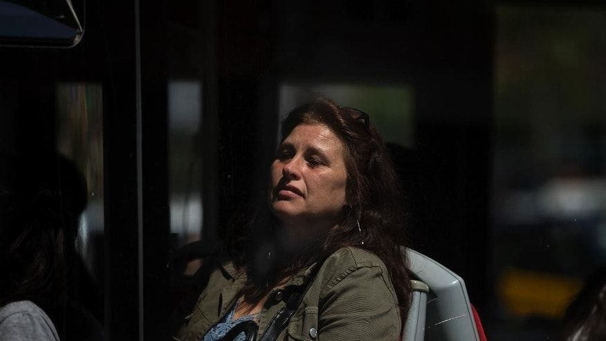 A woman sits inside a bus as it leaves a high school in Barcelona, Spain, Monday, April 20, 2015. A student walked into the Barcelona school Monday morning and killed a teacher and wounded several other high school students on the 16th anniversary of the massacre of students in shootings at Columbine High School in the U.S. state of Colorado. (AP Photo/Emilio Morenatti)