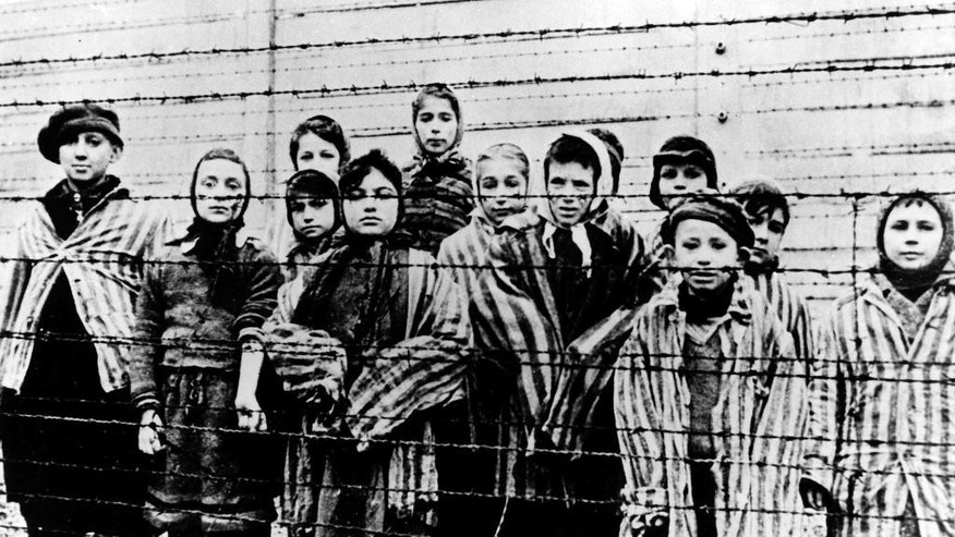 A picture taken just after the liberation by the Soviet army in January, 1945, shows a group of children wearing concentration camp uniforms behind barbed wire fencing in the Auschwitz Nazi concentration camp.