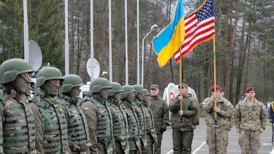 US and Ukrainian soldiers stand guard during opening ceremony of the 'Fiarles Guardian - 2015',  Ukrainian-US Peacekeeping and Security command and staff training, in western Ukraine, in  Lviv region, Monday, April 20, 2015. (AP Photo/Efrem Lukatsky)