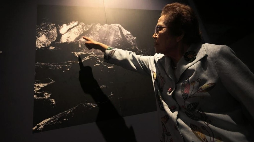 In this March 22, 2015 photo, Yoshiko Shimabukuro, a survivor of the Himeyuri Student Nurse Corps 70 years ago, points to a photo of the First Surgical Cave where she stationed in the battle of Okinawa during WWII at Himeyuri Peace Museum in Itoman on the southern Japanese island of Okinawa. Shimabukuro, head of the museum, who experienced the war's darkest moments, it's never been easy to reconcile the hatred of the past with the peace of the present. It took decades for Baker to open up about his experiences. Shimabukuro has spent her life teaching children the horrors of her personal battle and praying for the day when the 20,000 U.S. troops still based on her island will leave, once and for all. (AP Photo/Eugene Hoshiko)