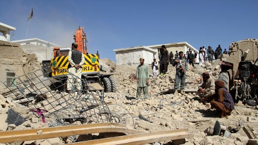 Afghan security forces work at the site of a bombing in Kandahar, south of Kabul, Afghanistan, Tuesday, April 21, 2015. Afghan officials say an explosion near a police station has killed several people and wounded over a dozen. Authorities initially believed a car bomb caused the explosion, but later said they were unsure what happened. (AP Photo)