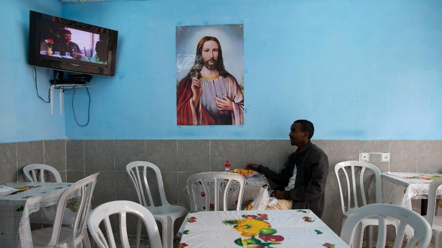 An African migrant sits at a restaurant in Tel Aviv, Israel, Tuesday, April 21, 2015. Tens of thousands of African migrants have made their way to Israel in recent years. Most of these migrants came from Eritrea, an eastern African nation with one of the world's most dismal human rights records. (AP Photo/Oded Balilty)