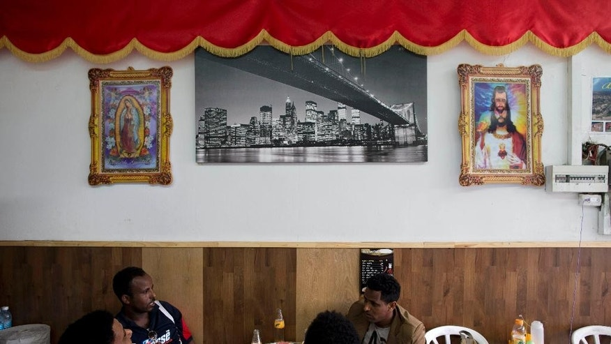 African migrants sit at a restaurant in Tel Aviv, Israel, Tuesday, April 21, 2015. Tens of thousands of African migrants have made their way to Israel in recent years. Most of these migrants came from Eritrea, an eastern African nation with one of the world's most dismal human rights records. (AP Photo/Oded Balilty)