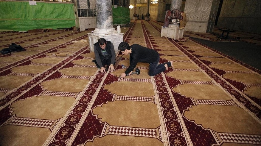 In this Sunday, April 19, 2015 photo, workers place new carpets at the Dome of the Rock shrine in Jerusalem. The Dome of the Rock enshrines the large rock slab where Muslim tradition says Mohammed ascended to heaven. Jews believe the rock may be where the holiest part of the two ancient temples stood about 2,000 years ago. (AP Photo/Mahmoud Illean)