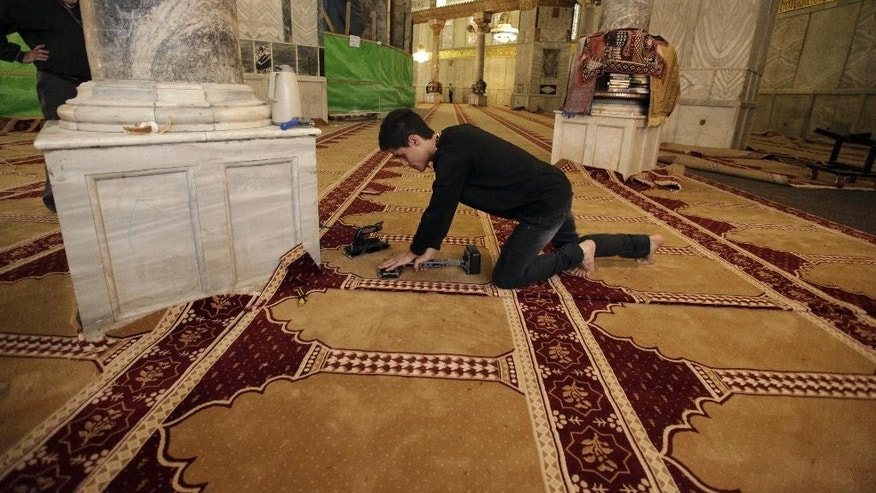 In this Sunday, April 19, 2015 photo a worker places new carpets at the Dome of the Rock shrine in Jerusalem. The Dome of the Rock enshrines the large rock slab where Muslim tradition says Mohammed ascended to heaven. Jews believe the rock may be where the holiest part of the two ancient temples stood about 2,000 years ago. (AP Photo/Mahmoud Illean)