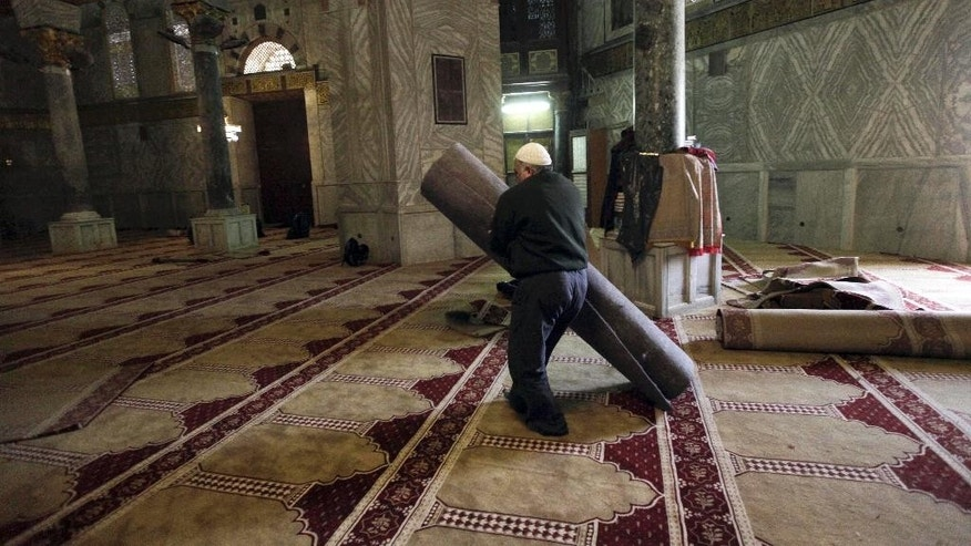 In this Sunday, April 19, 2015 photo, a worker carries new carpets at the Dome of the Rock shrine in Jerusalem. The Dome of the Rock enshrines the large rock slab where Muslim tradition says Mohammed ascended to heaven. Jews believe the rock may be where the holiest part of the two ancient temples stood about 2,000 years ago. (AP Photo/Mahmoud Illean)