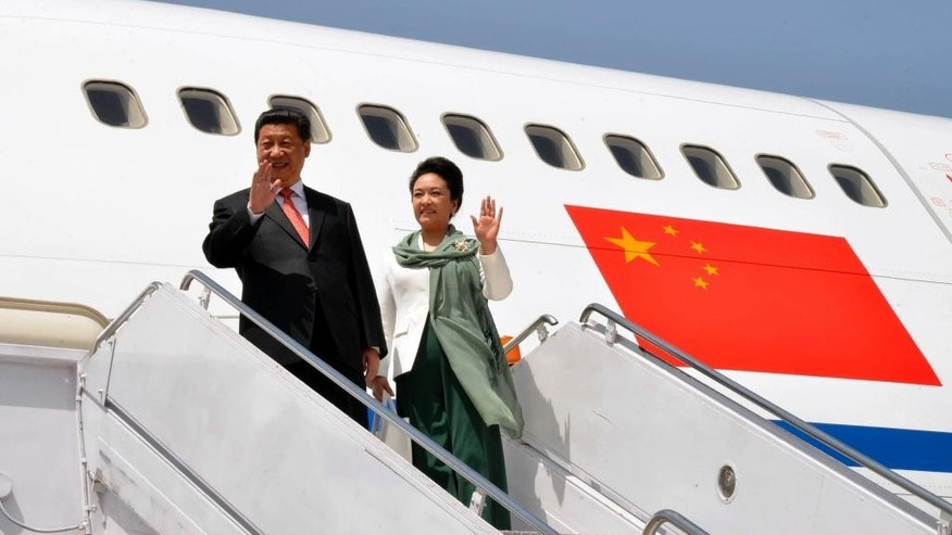 In this photo provided by Pakistan's Press Information Department, Chinese President Xi Jinping arrives with his wife Peng Liyuan at Nur Khan airbase in Islamabad, Pakistan, Monday, April 20, 2015. Xi arrived for a two-day visit during which the two sides will launch an ambitious $45 billion economic corridor linking Pakistan's port city of Gwadar with western China. (Press Information Department via AP)