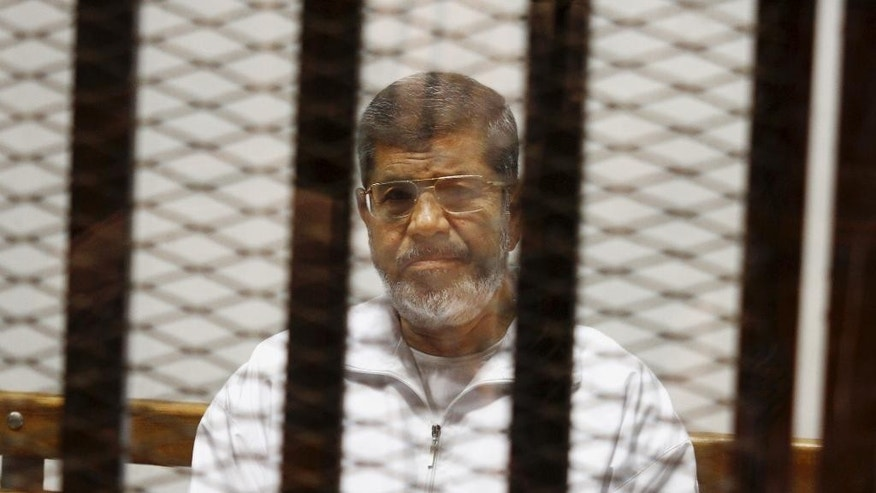 FILE - In this May 8, 2014 file photo, Egypt's ousted Islamist President Mohammed Morsi sits in a defendant cage in the Police Academy courthouse in Cairo, Egypt. On Tuesday April 21, 2015, an Egyptian criminal court  sentenced  Morsi to 20 years in prison over the killing of protesters in 2012, the first verdict to be issued against the leader. The case stems from violence outside the presidential palace in December 2012. (AP Photo/Tarek el-Gabbas, File)
