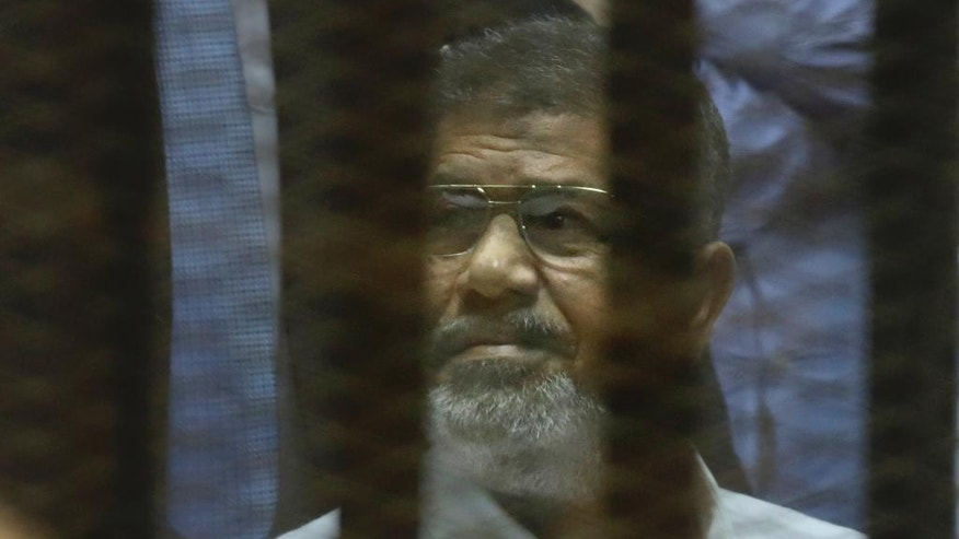 Egypt's ousted Islamist President Mohammed Morsi sits in a soundproof glass cage inside a makeshift courtroom at Egypt's national police academy in Cairo, Egypt, Tuesday, April 21, 2015. An Egyptian criminal court on Tuesday, sentenced Morsi to 20 years in prison over the killing of protesters in 2012, the first verdict to be issued against the country's first freely elected leader. (AP Photo/Amr Nabil)