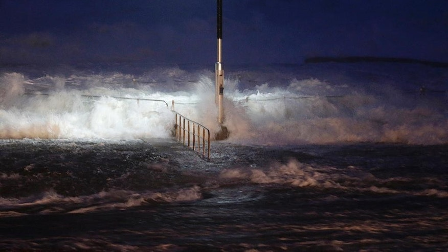 Huge waves crash over swimming baths at Avalon Beach in Sydney Australia Tuesday, April 21, 2015. A fierce storm lashing Australia's southeast destroyed homes, left dozens stranded in swirling floodwaters and may have led to the deaths of several people officials said Tuesday. (AP Photo/Glenn Nicholls)