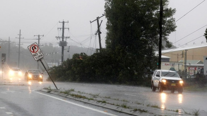 A tree and power lines lie across a major road in Raymond Terrace, approximately 150 kilometers (94 miles) north of Sydney, Australia, Tuesday, April 21, 2015. A fierce storm lashing Australia's southeast destroyed homes, left dozens stranded in swirling floodwaters and may have led to the deaths of three people officials said Tuesday. (Nikki Short/AAP Image via AP) AUSTRALIA OUT, NEW ZEALAND OUT, PAPUA NEW GUINEA OUT, SOUTH PACIFIC OUT, NO SALES, NO ARCHIVES