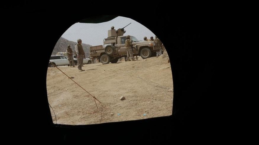 Saudi soldiers are seen through a tent positioned at the Saudi border with Yemen in Jazan, Saudi Arabia, Monday, April 20, 2015. The Saudi air campaign in Yemen is now in its fourth week. (AP Photo/Hasan Jamali)