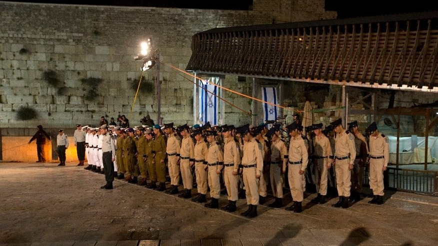 Israeli soldiers observe a minute of silence during a service marking Memorial Day at the Western Wall, the holiest site where Jews can pray, in Jerusalem's Old City, Tuesday, April 21, 2015.  Israelis marked Memorial Day starting Tuesday evening in remembrance of the nation's fallen soldiers. (AP Photo/Sebastian Scheiner)