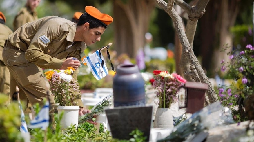 An Israeli soldier places a small national flag with a black ribbon on the grave of a fallen soldier on the eve of Memorial Day at the Kiryat Shaul military cemetery in Tel Aviv, Israel, Tuesday, April 21, 2015. Israel marks the annual Memorial Day in remembrance of soldiers who died in the nation's conflicts, beginning at dusk Tuesday until Wednesday evening. (AP Photo/Ariel Schalit)