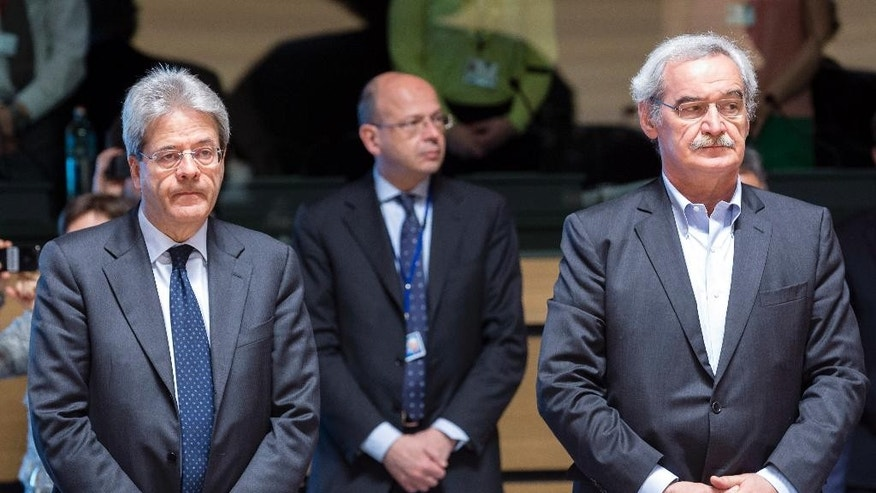 Italian Foreign Minister Paolo Gentiloni, left, and Greece's Deputy Foreign Minister Nikos Chountis stand for a moment of silence during a meeting of EU foreign ministers at the EU Council building in Luxembourg on Monday, April 20, 2015. An Italian coast guard ship headed toward Sicily Monday to look for survivors of a capsized ship in what could be the Mediterranean's deadliest migrant tragedy, as EU foreign ministers gathered for an emergency meeting to discuss the crisis. (AP Photo/Thierry Monasse)