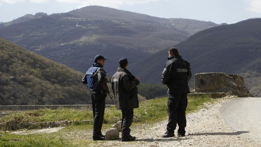 Police officers look towards the Macedonian mountain village of Gosince from a police check point set near the northern Macedonian  border with Kosovo, on Tuesday, April 21, 2015. Macedonian police say a group of about 40 people wearing uniforms of the disbanded Kosovo Liberation Army, or UCK, have attacked a police watchtower in Gosince early Tuesday, on the country's northern border with Kosovo. (AP Photo/Boris Grdanoski)
