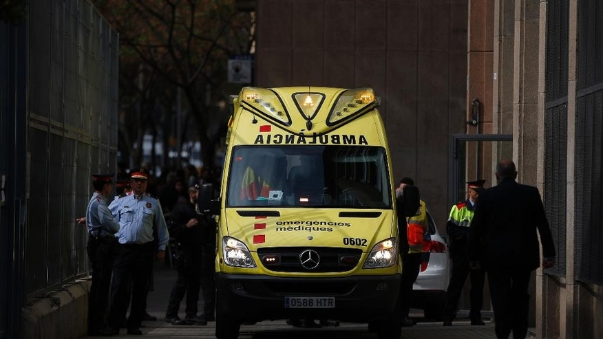 An ambulance waits outside a school in Barcelona, Spain, Monday, April 20, 2015. A student walked into the Barcelona school Monday morning and killed a teacher and wounded several other high school students on the 16th anniversary of the massacre of students in shootings at Columbine High School in the U.S. state of Colorado. (AP Photo/Emilio Morenatti)