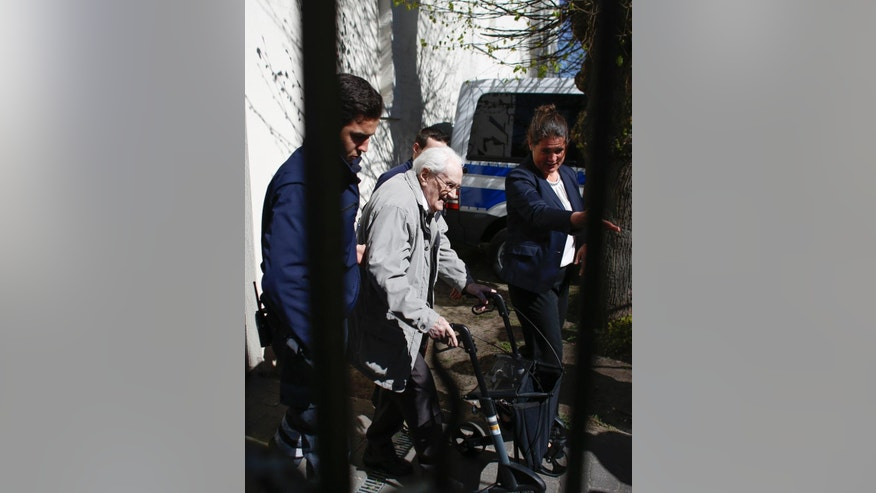 Former SS guard Oskar Groening, center, leaves the court building after the first day of the trial against him in Lueneburg, northern Germany, Tuesday, April 21, 2015. The 93-year-old former Auschwitz guard faces trial on 300,000 counts of accessory to murder, in a case that will test the argument that anyone who served at a Nazi death camp was complicit in what happened there. (AP Photo/Markus Schreiber)
