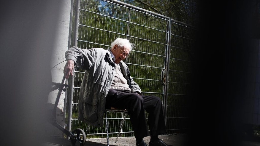 Former SS guard Oskar Groening sits behind a fence during the noon break of the trial against him in Lueneburg, northern Germany, Tuesday, April 21, 2015.  93-years-old Groening faces 300,000 counts of accessory to murder at the trial, which will test the argument that anyone who served as a guard at a Nazi death camp was complicit in what happened there. Groening said he bears a share of the moral guilt for atrocities at the camp, but told judges it is up to them to decide whether he deserves to be convicted as an accessory to murder.  (AP Photo/Markus Schreiber)