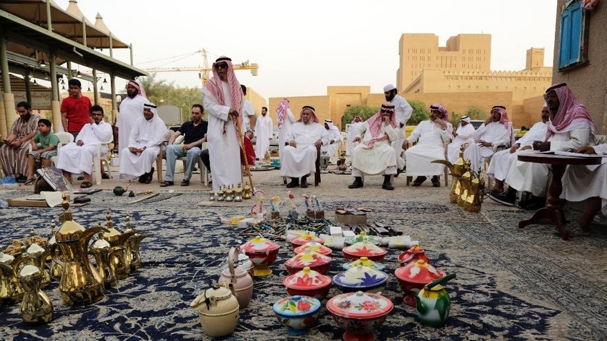 In this April 16, 2015 photo, traditional coffee pots, left, and colorful clay dishes are on display at al-Aqeeliya open-air auction market in Riyadh, Saudi Arabia. The market is far from the upscale malls and designer boutiques found in other parts of the capital, where haggling over the price is unacceptably un-chic. (AP Photo/Hasan Jamali)
