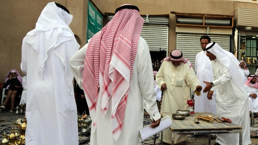 In this April 16, 2015 photo, Saudi men bargain to buy traditional Saudi swords and daggers at al-Aqeeliya open-air auction market in Riyadh, Saudi Arabia. Souvenir swords that sell as decorative pieces can go for more than 40 Saudi riyals ($10) in one of the market's stalls, but at the auction a whole bundle of 10 or more sells for 100 riyals ($27) to the highest bidder. (AP Photo/Hasan Jamali)