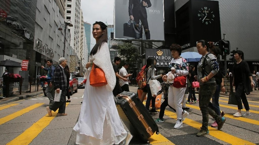 In this Sunday, April 12, 2015 photo, a mainland Chinese tourist carries a suitcase as she walks at a shopping district in Hong Kong. Eighteen years after this world financial hub returned from colonial British control to Chinese rule, many say they feel more alienated and less trusting than ever of the central Chinese government and even the people visiting from across the border. The complaints range from the small to the sweeping, from the perceived rudeness of Chinese tourists to fears that leaders in Beijing are sabotaging the freedoms and rule of law that have long distinguished Hong Kong from the rest of China. (AP Photo/Vincent Yu)