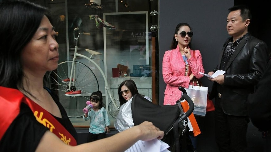 In this Sunday, April 12, 2015 photo, a woman who supports shoppers from the mainland China delivers leaflets in front of some mainland Chinese tourists who are queuing up outside a luxury brand boutique at a shopping district in Hong Kong. Eighteen years after this world financial hub returned from colonial British control to Chinese rule, many say they feel more alienated and less trusting than ever of the central Chinese government and even the people visiting from across the border. The complaints range from the small to the sweeping, from the perceived rudeness of Chinese tourists to fears that leaders in Beijing are sabotaging the freedoms and rule of law that have long distinguished Hong Kong from the rest of China. (AP Photo/Vincent Yu)