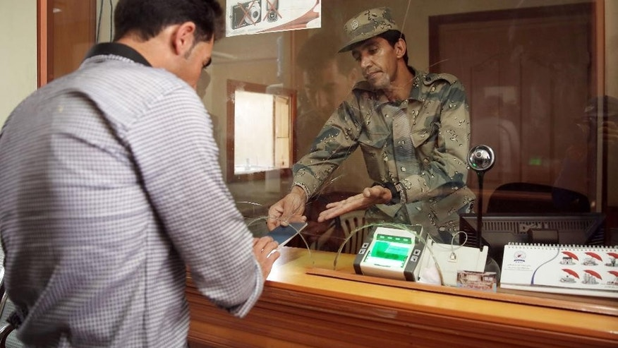 "In this Monday, April 13, 2015 photo, a border police officer returns the passport of a returnee, at the Afghanistan-Iranian border point on the outskirts of Islam Qala in Herat province, west of Kabul, Afghanistan. Around 25,000 Afghans a month are deported from Iran at Islam Qala, nicknamed ""Zero Point"" along with another 30,000 a month who cross returning home voluntarily, a sign of Tehran's efforts to control the huge numbers of Afghans who flock to their neighbor. Iran has long been an outlet for Afghans, either searching for work to escape poverty or seeking refuge from their country's chronic wars and instability. (AP Photo/Massoud Hossaini)"