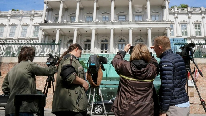 Journalists wait in front of  a luxury downtown hotel, where closed-door nuclear talks with Iran take place, in Vienna, Austria, Wednesday, April 22, 2015. Negotiators are meeting in attempts to reach a deal that curbs Iran's nuclear program in exchange for sanctions relief. (AP Photo/Ronald Zak)