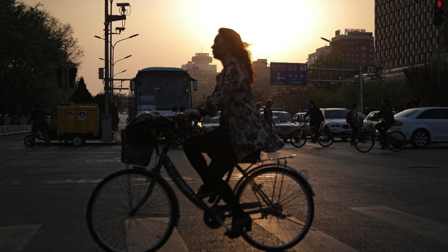 People ride bicycles past a busy traffic on Chang'an Avenue during a rush hour in Beijing Wednesday, April 22, 2015. A key measure of air pollutants in China's capital showed 19 percent drop in the first three months of the year, local authorities said Wednesday. (AP Photo/Andy Wong)