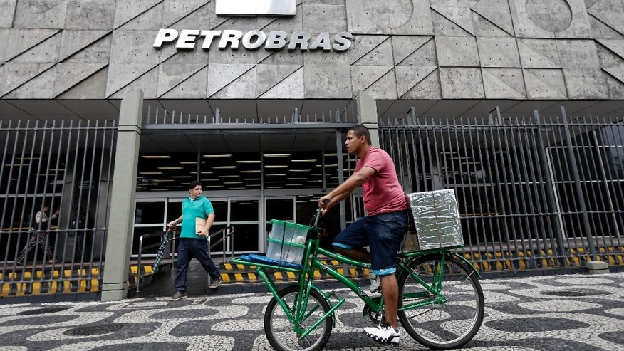 A man rides a bike in front of the Petrobras headquarters in Rio de Janeiro, Brazil, Wednesday, April 22, 2015. Brazil's state-run oil company Petrobras says it lost $2.1 billion because of inflated contracts and other costs related to a long-running kickback scheme. Federal prosecutors have called the scheme the biggest corruption case ever uncovered in Brazil. They stress that they are still investigating and says the scope of the case continues to widen. (AP Photo/Silvia zquierdo)