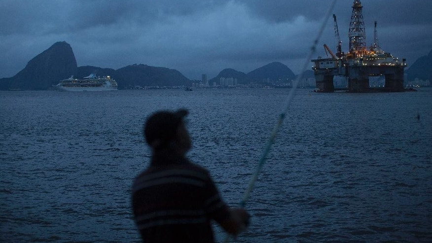 A man fishes backdropped by the Sugar Loaf Mountain, left, and an oil platform that floats in the waters of the Guanabara bay in Niteroi, Brazil, Tuesday, April 21, 2015. Brazil's state-run oil company Petrobras says it lost $2.1 billion because of inflated contracts and other costs related to a long-running kickback scheme. Federal prosecutors have called the scheme the biggest corruption case ever uncovered in Brazil. They stress that they are still investigating and says the scope of the case continues to widen. (AP Photo/Leo Correa)