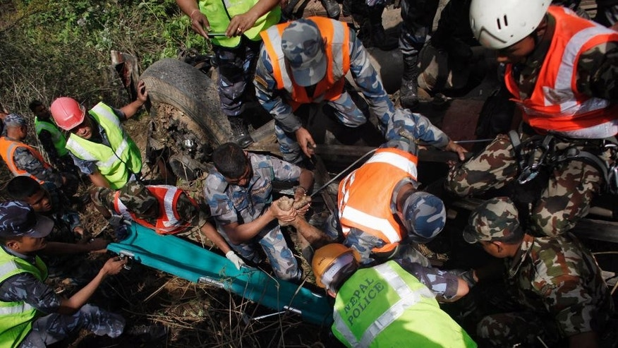 Nepalese rescue workers retrieve the dead body of a victim at the site of a bus accident, about 16 kilometers (10 miles) west of Kathmandu, Nepal, Wednesday, April 22, 2015. The bus, carrying Hindu pilgrims from the Indian state of Gujrat on a visit to the Pashupatinath temple, plunged off a mountain highway near Nepal's capital on Wednesday. (AP Photo/Niranjan Shrestha)