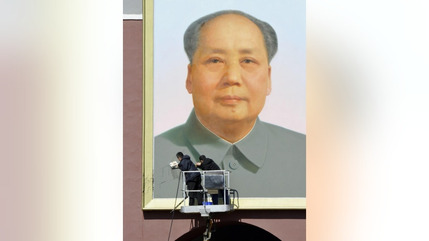 In this March 6, 2014 file photo, workers clean black marks off the portrait of late communist leader Mao Zedong which hangs on Tiananmen Gate in Beijing, China.