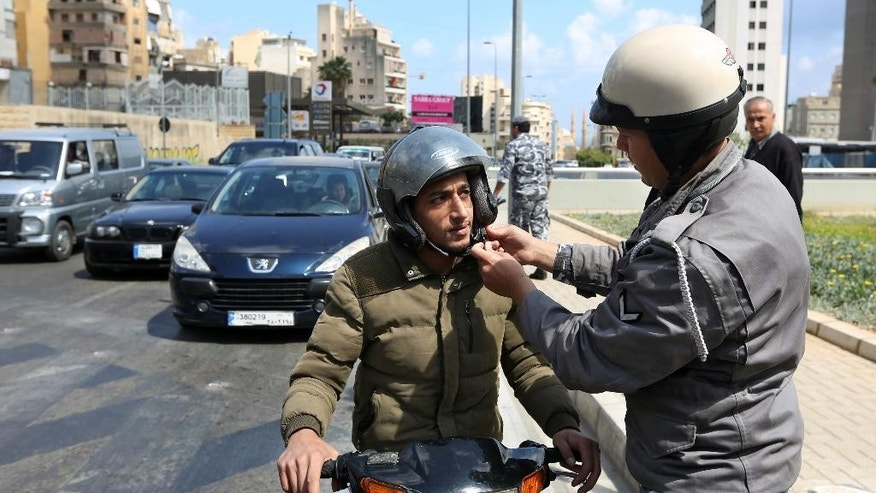 A Lebanese traffic policeman helps adjust the helmet of a motorist, in Beirut, Lebanon, Wednesday, April 22, 2015. Lebanon has started implementing a new traffic law that includes speed limits and mandatory seat belts in what officials hope is a move that will reduce deaths from road accidents. (AP Photo/Bilal Hussein)