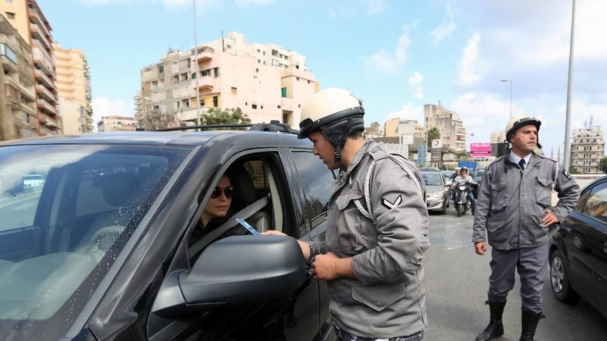 A Lebanese traffic policeman hands over pamphlets to a driver on the new traffic law, in Beirut, Lebanon, Wednesday, April 22, 2015. Lebanon has started implementing a new traffic law that includes speed limits and mandatory seat belts in what officials hope is a move that will reduce deaths from road accidents. (AP Photo/Bilal Hussein)