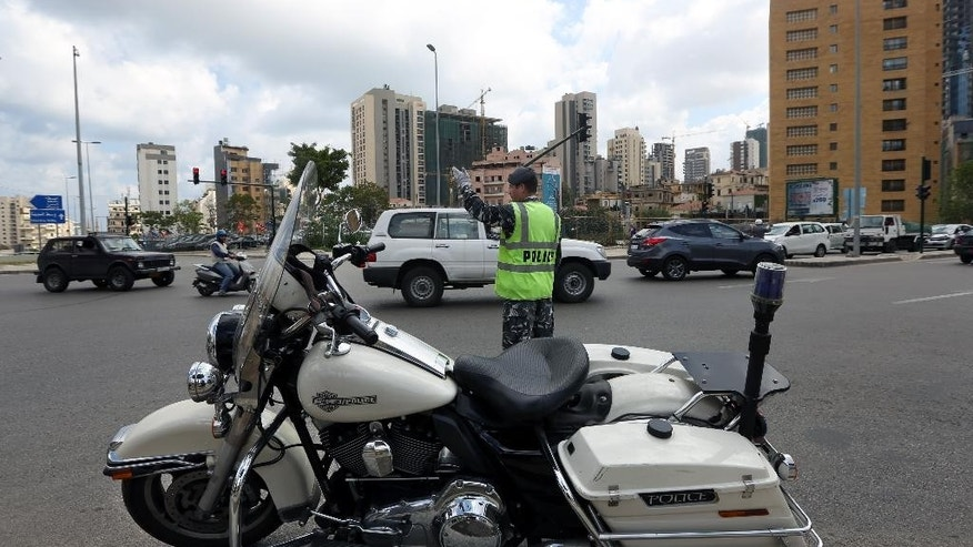 A Lebanese traffic policeman directs traffic on an intersection in Beirut, Lebanon, Wednesday, April 22, 2015. Lebanon has started implementing a new traffic law that includes speed limits and mandatory seat belts in what officials hope is a move that will reduce deaths from road accidents. (AP Photo/Bilal Hussein)