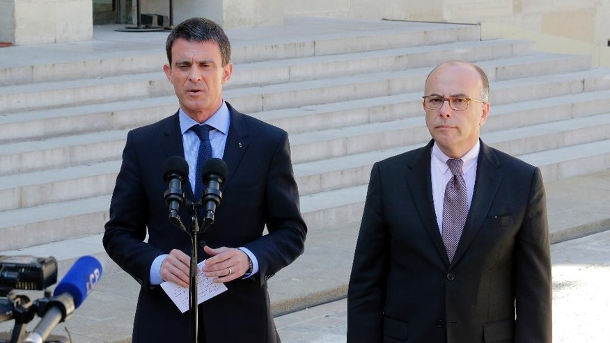 CAPTION CORRECT, CORRECTS SPELLING OF NAME AND DATE - French Prime Minister Manuel Valls, left, and interior minister Bernard Cazeneuve, address the media after a cabinet meeting at the Elysee Palace in Paris, France, Wednesday, April 22, 2015. An Islamic extremist with an arsenal of heavy weapons planned an imminent attack on one or more French churches, France's top security official said Wednesday, announcing the arrest of the man who is also accused in the death of a young mother, Aurelie Chatelain, a 32-year-old Frenchwoman visiting Paris for a training session for her work. (AP Photo/Jacques Brinon)