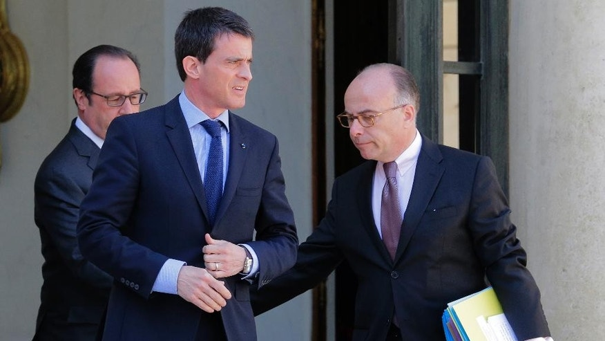 CAPTION CORRECT, CORRECTS SPELLING OF NAME AND DATE - French Prime Minister Manuel Valls, center, and interior minister Bernard Cazeneuve, right, leaves the Elysee Palace in Paris, France, after a cabinet meeting while French President Francois Hollande, Wednesday, April 22, 2015. An Islamic extremist with an arsenal of heavy weapons planned an imminent attack on one or more French churches, France's top security official said Wednesday, announcing the arrest of the man who is also accused in the death of a young mother, Aurelie Chatelain, a 32-year-old Frenchwoman visiting Paris for a training session for her work. (AP Photo/Jacques Brinon)