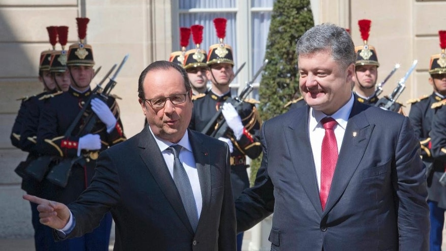 French President Francois Hollande, left, welcomes  Petro Poroshenko, President of Ukraine, in the courtyard of the Elysee Palace  in Paris, France, Wednesday, April 22, 2015.  Poroshenko is set to discuss current developments in Ukraine with the French President. (AP Photo/Jacques Brinon, Pool)
