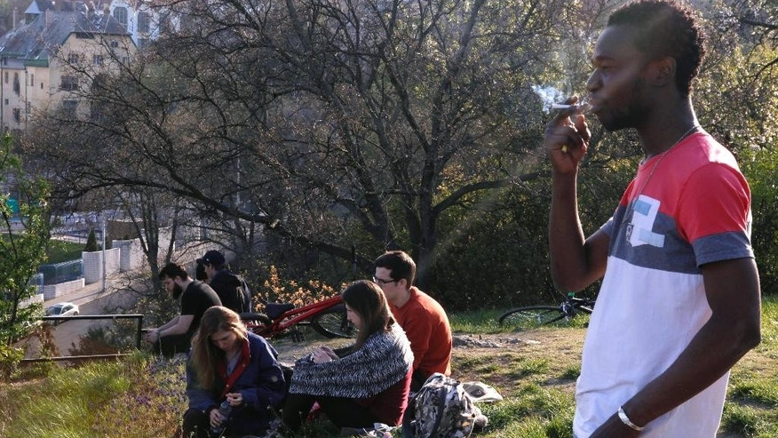 In this photo taken Thursday, April 9, 2015, Ivorian Jean Paul Apetey, 34, smokes a cigarette on top of Budapest's Gellert Hill two days after arriving to Hungary after a grueling month long journey across the Balkans. Hungary is the most popular back door for tens of thousands of migrants annually who want to breach the perimeter of the European Union without obvious risk of death. Their long journey through the Balkans, often on foot and at night, proves to be full of disappointment and danger, but not the mortal peril of a North African sea crossing to Italy - a journey that has produced more than a thousand dead in the southern Mediterranean this month alone. (AP Photo/Dalton Bennett)