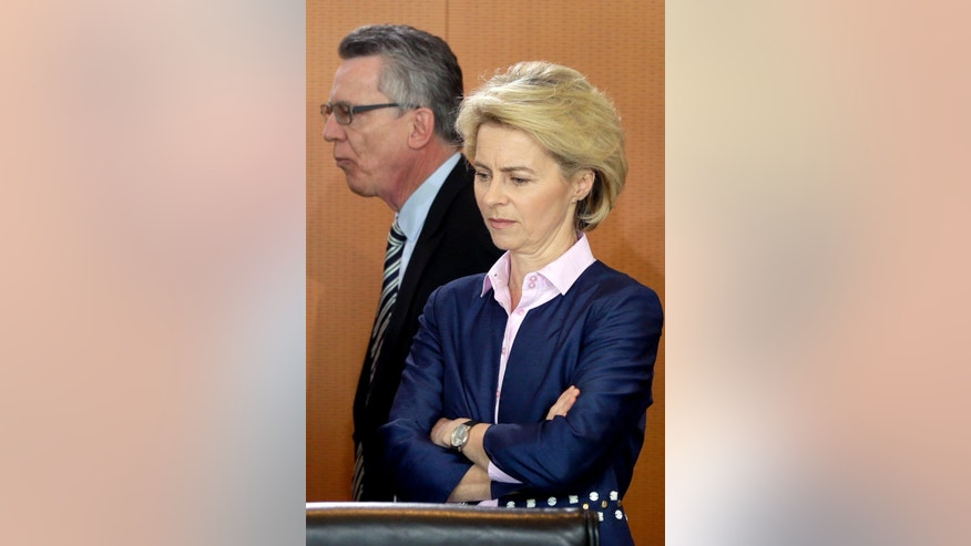 German Interior and former Defense Minister Thomas de Maiziere, rear, walks past German Defense Minister Ursula von der Leyen, front, at the beginning of the weekly cabinet meeting at the chancellery in Berlin, Germany, Wednesday, April 22, 2015. (AP Photo/Michael Sohn)