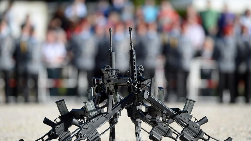 "FILE - In this June 5, 2014 file photo G36 rifles of manufacturer Heckler&Koch stand in front of soldiers in Sigmaringen, southern Germany. The widely used assault rifle has ""no future"" with the German military in its current form, Germany's defense minister Ursula von der Leyen said Wednesday, April 22, 2015, escalating a dispute over the weapon's alleged shortcomings. (Patrick Seeger/dpa via AP, File)"