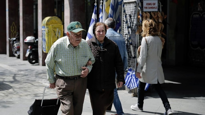 An elderly couple walk in central Athens, on Wednesday, April 22, 2015. Greece is running perilously short of cash amid an impasse in bailout talks with its international creditors. Eurozone finance ministers are to meet in Riga, Latvia on Friday but hopes of a deal on Greece there have diminished. (AP Photo/Petros Giannakouris)