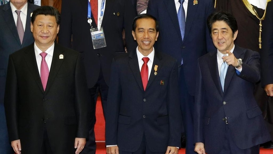 Indonesian President Joko Widodo, center, Chinese President Xi Jinping, left, and Japanese Prime Minister Shinzo Abe prepare for a group photo during the Asian African Summit in Jakarta, Indonesia, Wednesday, April 22, 2015. (AP Photo/Dita Alangkara)