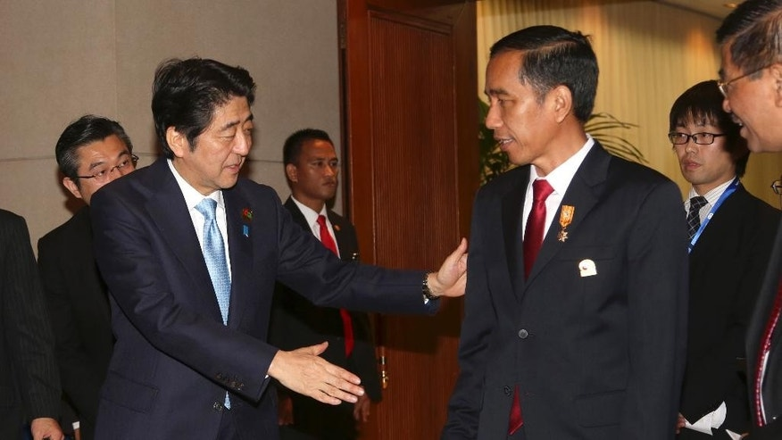 Japanese Prime Minister Shinzo Abe, left, shakes hands with Indonesian President Joko Widodo after their bilateral meeting on the sideline of the Asian African Summit in Jakarta, Indonesia, Wednesday, April 22, 2015. (AP Photo/Tatan Syuflana, Pool)