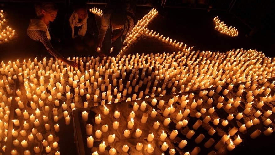 Hundreds of candles are lit during a silent vigil outside the Constitutional Court in Johannesburg, Tuesday, April 21, 2015. The vigil was held in an effort to take a stand against the ongoing immigrant attacks in South Africa as the army has been deployed to areas that remain volatile after a spate of attacks targeting foreign nationals. (AP Photo/Denis Farrell)