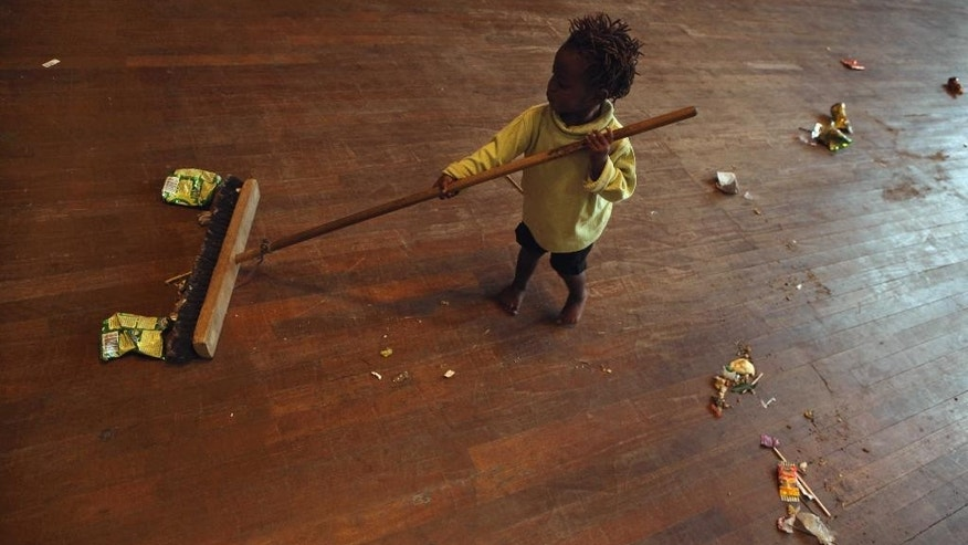 A child plays with a broom at a shelter for victims of immigrant attacks in Johannesburg, Wednesday, April 22, 2015. No new incidents of violence targeting foreigners were reported overnight in Johannesburg or in the coastal city of Durban, where the attacks began, police said. (AP Photo/Denis Farrell)