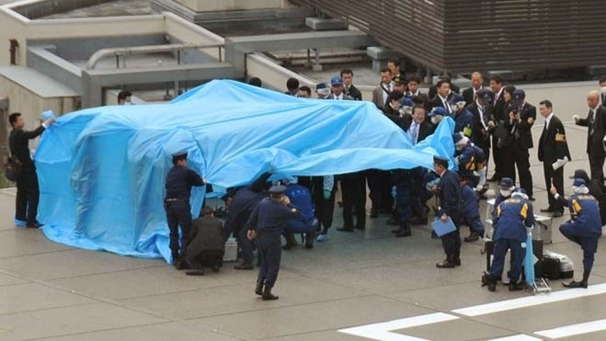 April 22, 2015: Investigators gather around a small drone covered with blue sheets on the roof of Prime Minister Shizo Abe's official residence in Tokyo.