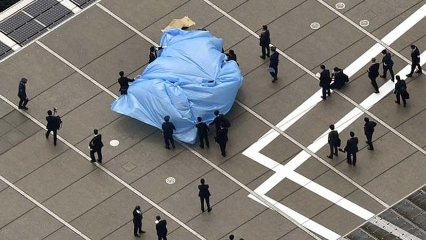 April 22, 2015: Investigators gather around a small drone covered with blue sheets, on the roof of Prime Minister Shizo Abe's official residence in Tokyo.